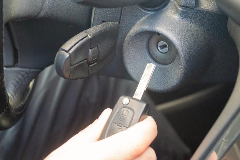 hand holding car key near ignition